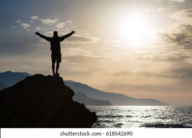 Man with arms outstretched celebrating or praying in beautiful inspiring sunrise with mountains and sea. Man hiking or climbing with hands up enjoy inspirational landscape on rocky top on Crete.