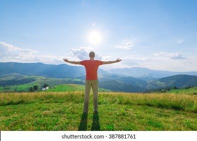 Man with arms outstretched in mountains at sunny summer day