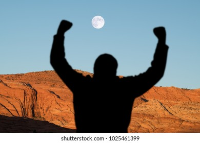 Man with arms raised in a desert canyon with full moon setting.