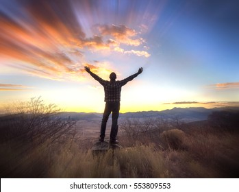 Man with arms raised, looking out over valley