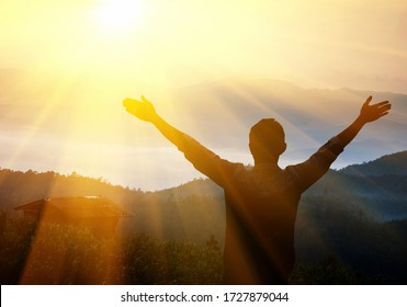 Man with arms raised at sunset. Young man at sunset raises his hands up
