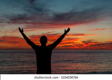 Man with arms up wide open silhouette on sea sunset. Travelling alone. Meditative nature and human concept.