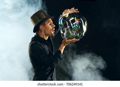 Man artist blowing many soap bubble. Soap bubble show in black studio.