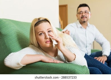 Man asking for forgiveness from despair woman after quarrel at home. Focus on girl