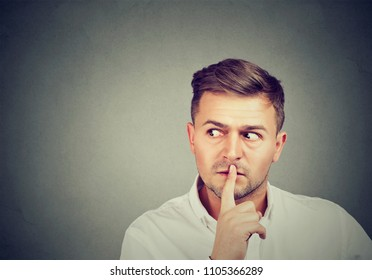 Man asking for silence and secrecy holding finger on lips and looking away in conspiracy