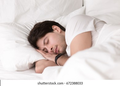 Man is asleep in cozy white bed at night, handsome young guy sleeping at home with wearable electronic device smart watch on his wrist for sleep tracking, monitoring heart rate for healthcare