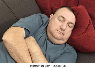 man asleep on a sofa