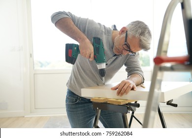 Man assembling DIY furniture using electric drill