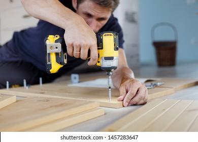 Man assembling furniture at home using a cordless screwdriver
