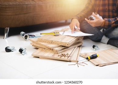 The man assembling new furniture at his home.
