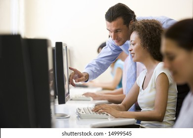 Man assisting woman in computer room