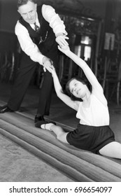 Man assisting young girl doing front split