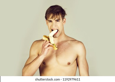 man or athlete with blond hair, stylish haircut and naked muscular chest, biceps, triceps eating banana, vitamin fruit on grey background. Health, dieting, fitness