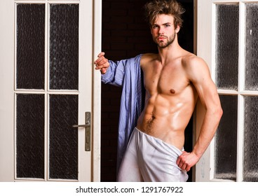 Man athlete with fit sexy torso. Sexy lover concept. Sexy attractive macho tousled hair coming out through bedroom door. Bachelor sexy body chest and belly. Guy shimmering sweaty skin wear bathrobe.