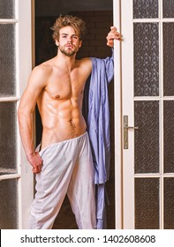 Man athlete with fit sexy torso. Sexy lover concept. Bachelor sexy body chest and belly. Sexy attractive macho tousled hair coming out through bedroom door. Guy shimmering sweaty skin wear bathrobe.