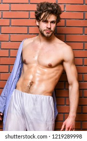 Man athlete with fit torso. Guy shimmering skin undressing bathrobe. Sportsman show six pack sexy torso. Bachelor sexy body chest and belly. Sexy attractive macho tousled hair on wooden background.