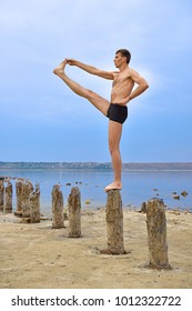 Man Athlete Makes A Stand On Wooden Pillars.
