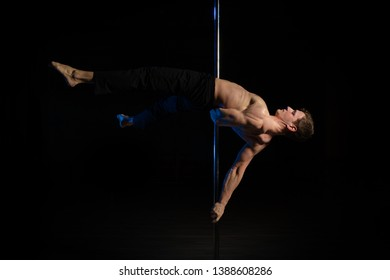 A man athlete performs exercises on the pole on the stage in the dark