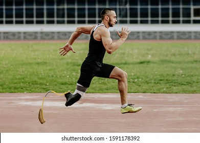 man athlete with prosthetic legs running in track stadium