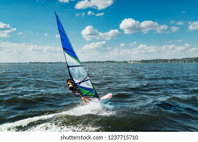 the man athlete rides the windsurf over the waves on the lake