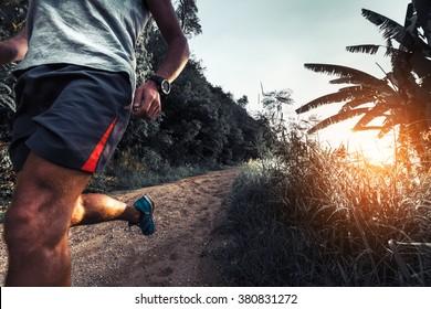 Man athlete running on the gravel road