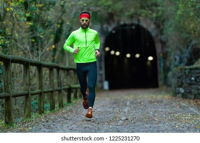 Man athlete runs on bike path between tunnels in the fall.