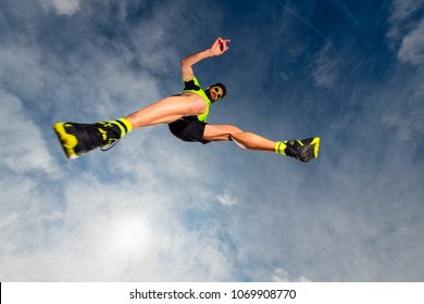 Man athlete while jumping during a trail running in the mountains.