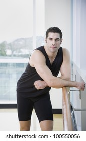 Man in athletic gear leaning on ballet bar