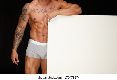 Man with athletic muscular body holding blank notice board