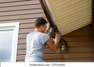 man attaches gutter on the roof of the porch