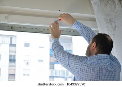 Man attaching elements with a screwdriver in order to install a blind