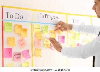 Man attaching sticky note to scrum task board in office