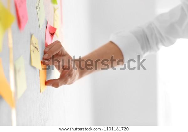 Mann, der im Büro eine klebrige Notiz an die Taskleiste anbringt