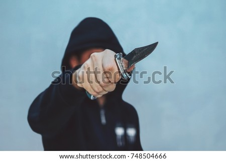 man attack with knife. The guy with the knife in hand wearing a black hood. The threat of a cold weapon. The concept of crime and robbery.