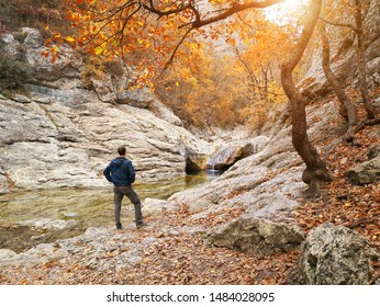Man in autumn forest and river. Landscape and nature scene.