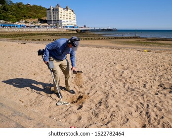 Man in autumn outfit walking the beach with a metal detector sifting through sand looking for tresors on the coastal town on Llandudo, Wales.  September 21, 2019.