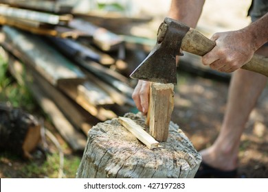 Man with an ax chops firewood. Man is chopping wood with vintage axe
