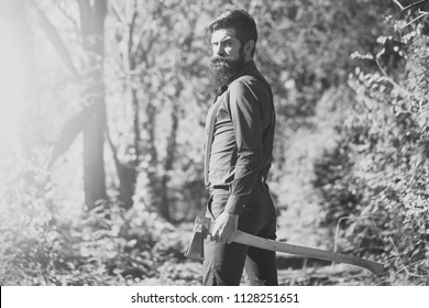 man with an ax. One handsome strong stylish male logger of young man with long lush black beard and moustache in shirt holding wooden axe standing in forest outdoor on natural background, horizontal