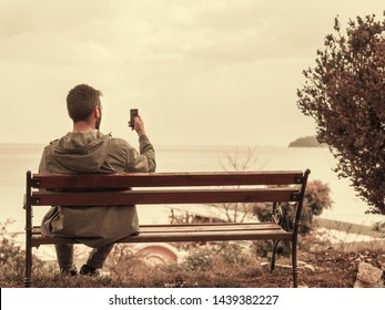 Man with back looking at phone screen while sitting on a bench outside, outdoors in the park  near the sea