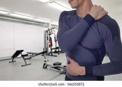 Man with back and neck pain in gym. Sports exercising injury.