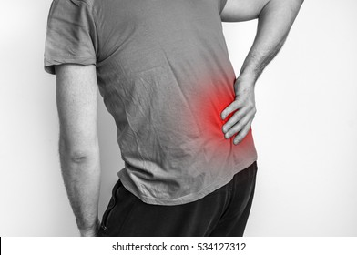 Man with back pain holding aching part - black and white photo