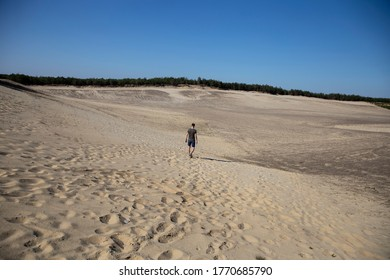 Man from back walking in huge sand beach. Interesting nature landscape, man versus environment. Nature wonder.