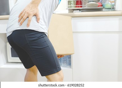 Man with backache while lifting box in the warehouse Health concepts and back bone
