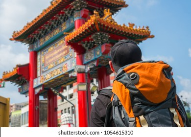 Man with backpack in Asia with chinese gate in background in Chinatown in Bangkok Thailand