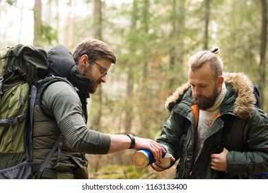 Man with a backpack and beard and his friend hiking in forest in autumn.