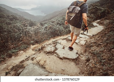 Man with backpack and camera is hiking by the stone path in the beautiful nature. There are fog and mountains at background.