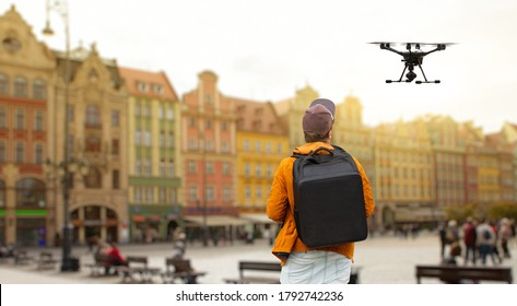 A man with a backpack controls a drone on a background of a European city