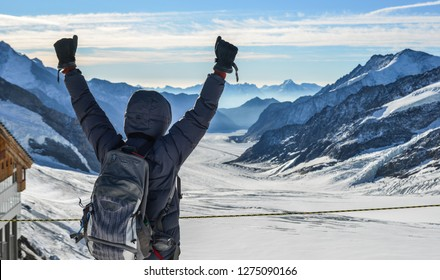 A man with backpack enjoying on snow peak of Jungfraujoch, Switzerland.