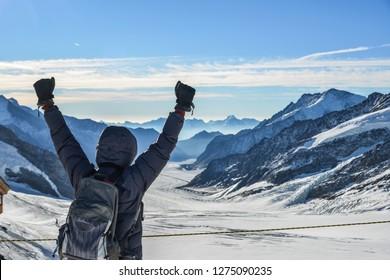 A man with backpack enjoying on snow peak of Jungfraujoch, Switzerland.
