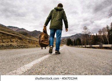 man with backpack in hand walking alone down a mountain road